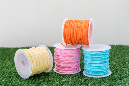 Four of colorful thread on grass with white background