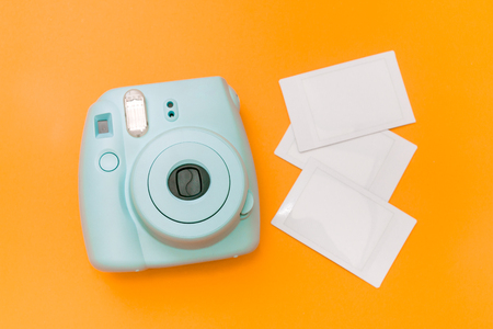 Blue mint instant camera with three films on orange background
