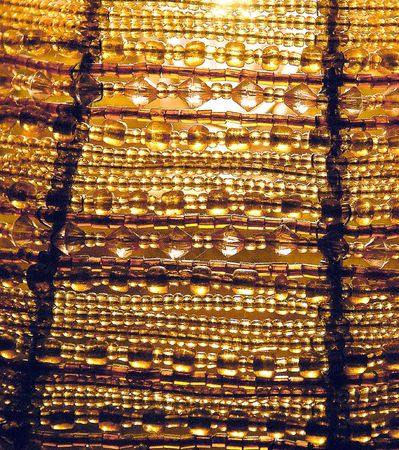 Amber beads of a lampshade with light in background