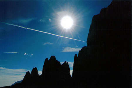 entrails: Silhouette of rock formations in Garden of the Gods against blue sky and bright white sun
