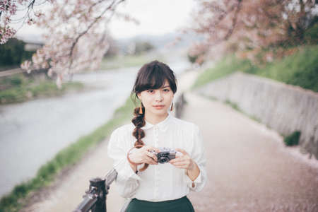A woman in a white shirt who has a camera with cherry blossoms