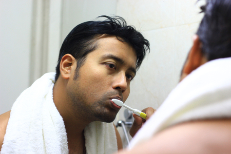 indian asian man looking after his appearance in front of a mirror beauty styling lifestyle. brushing routine