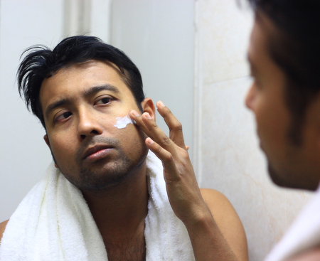 man looking after his appearance in front of a mirror beauty styling lifestyle