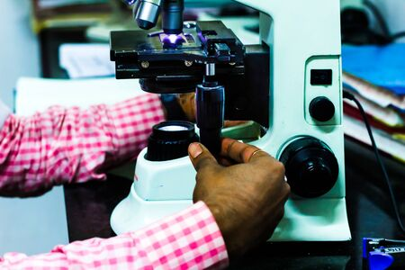 scientist adjusting knobs of a light microscope Stock Photo