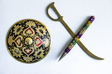 pen is mightier than sword concept by decorated round sword shield and pen in white background.antique artefact