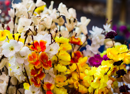 plastic flowers yellow white and orange for decoration Banco de Imagens