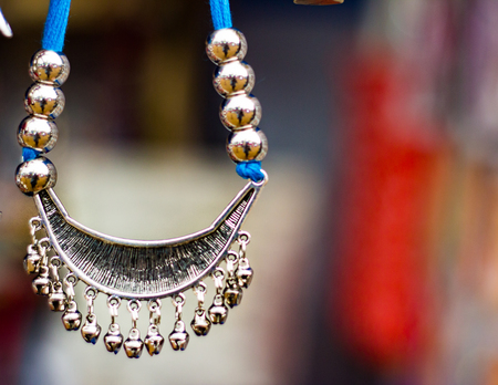 Silver necklace hanging for sale against a blurred background. Junk jewelry. Stock Photo - 100560160