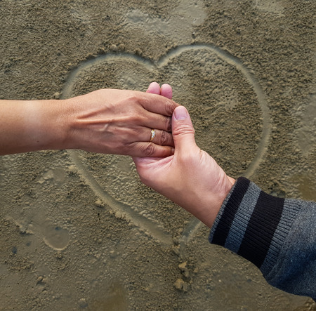 romantic couple on date holding hands on heart sign background drawn on wet beach sand Stock Photo