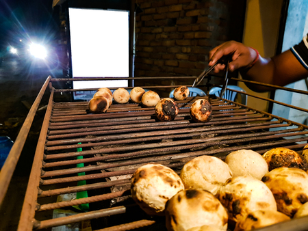 litti, a common north indian food is being baked road side on a coal grill by vendor with white mockup ad space in the background