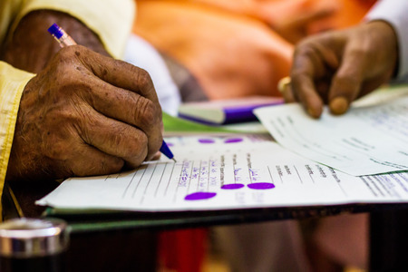 hand of an old man writing important legal document Stock Photo