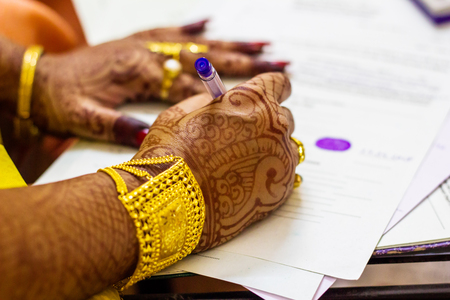 a newly married indian bengali wife with golden ornament and blacelet signing marriage registration form