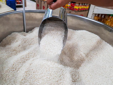 hand pouring raw uncooked heap of rice with measuring mug dispensing container at supermarket for sale
