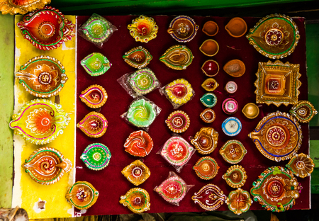 Different varieties of colourful diyas and diwali lamps for sale in a grocery shop Stock Photo