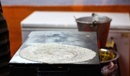 Making of paper plain Dosa on a tawa pan by spreading dosa batter mix of rice and dal and oiling on the thin sheet