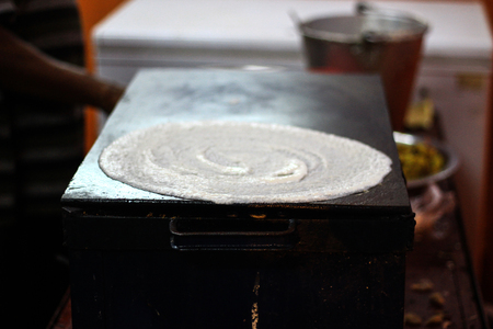 Making of Dosa on a tawa pan by spreading dosa batter mix of rice and dal Stock Photo