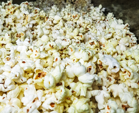 white salted pop corn heaped for sale. close up view