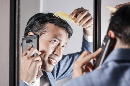 asian man in suit looking after his appearance in front of a mirror beauty styling lifestyle. Stock Photo