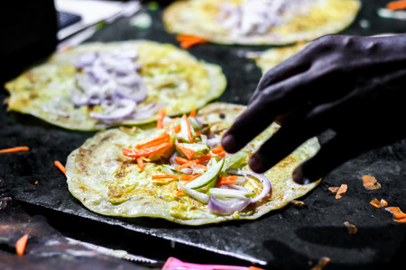 making of egg roll on a hot frying pan with oil and paratha and salad