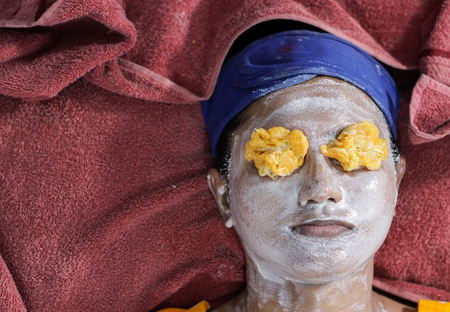 facial pack mask applied on face of a lady with hair band with eyes closed with orange pulp. herbal facial Stock fotó