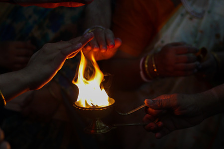 hands taking warmth of Divine diya holy flame of hindu god worship puja for blessings