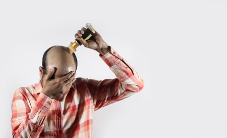 bald man covering his face and applying hair grow oil in white background with space for text