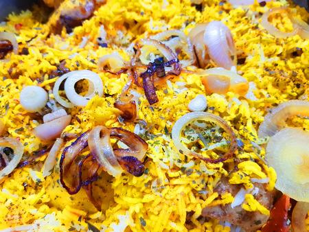 close up photo of hyderabadi dum handi biryani garnished with onions