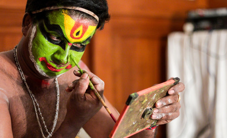 katakhali dance performer doing face paint and makeup in front of hand held mirror