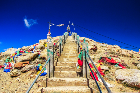 steep rock stairs with colourful flags rising up with deep blue sky