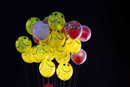 smile emoji shaped yellow balloon and heart shaped red balloons tied in bunch with threads in black background