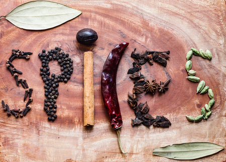 Typical ingredients for a garam masala black peppercorns, mace, cinnamon, cloves, dried red chilli and green cardamom in a wooden background 写真素材
