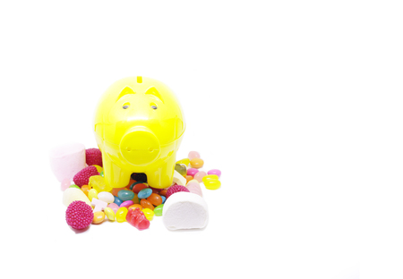 piggy bank and multi colored sugar candy in white background with space for text Reklamní fotografie