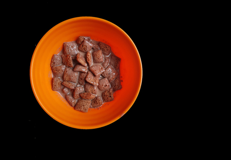 chocolate cornflakes dipped in chocolate milk in a white bowl in black background
