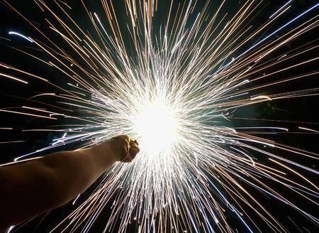 Hand charki, una mano de fuegos artificiales que emite chispas circulares en fondo negro Foto de archivo