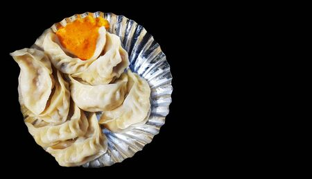 a plate of veg steamed momo with sauce chutney in black background with space for text Reklamní fotografie