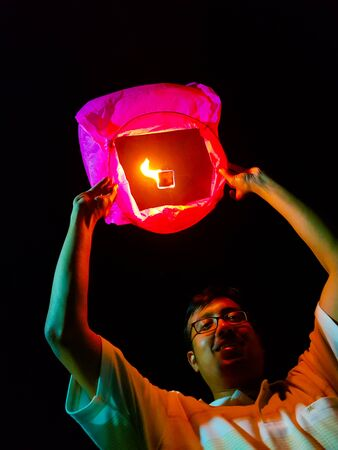 an indian man releasing a lighted paper hot air balloon in sky lantern festival Stock Photo