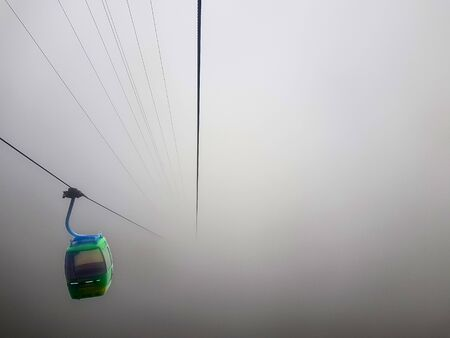 a cable car suspended in a cable in a very foggy weather with zero visibility Reklamní fotografie - 125074312