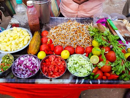 indian street food vendor selling spicy chickpea bengal gram chole mixture garnished with freshly cut onion,cucumber chilli and tomato 写真素材