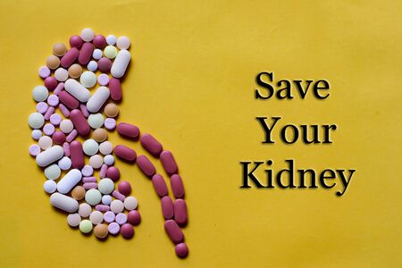 Medicine pills tablets capsules in shape of human kidney in yellow background with space for text