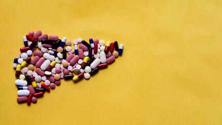 Kapsułki tabletek tabletek w kształcie ludzkiej wątroby na żółtym tle z miejscem na tekst Zdjęcie Seryjne