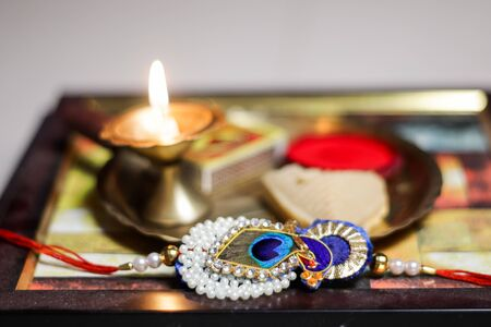 a plate thali decorated with rakhi sweet lamp diya for the occasion of rakshabandhan greeting of brother and sister