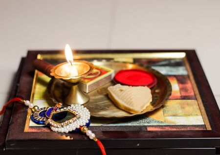 a plate thali decorated with rakhi sweet lamp diya for the occasion of rakshabandhan greeting of brother and sister Stock Photo