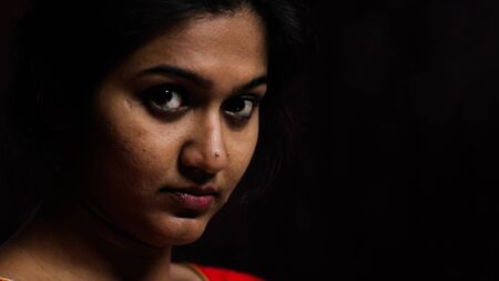 an indian female staring at the camera with thoughtful expression in black background with selective focus on rear eye Фото со стока