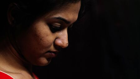 an indian female staring down in worry and depression in black background with selective focus on nose