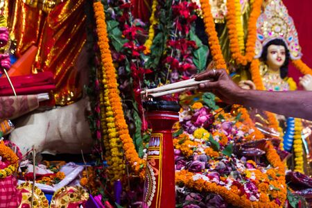 hand of a priest worshiping hindu god with garland and flower and fire Stockfoto