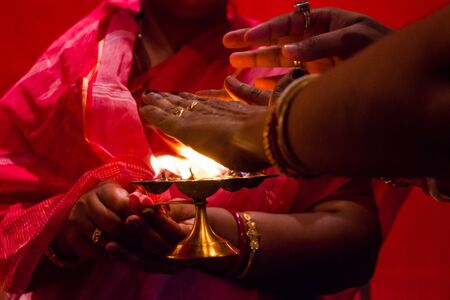 hands taking flame heat, a ritual of blessings in hindu god worship