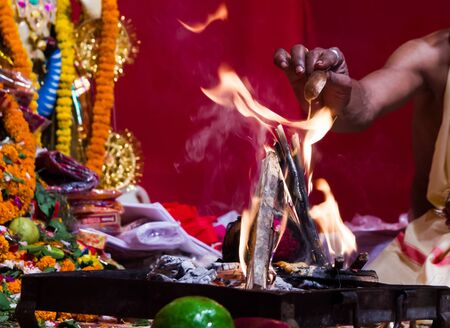hand of a priest worshiping hindu god with fire and yagna ritual by adding fuel in flame