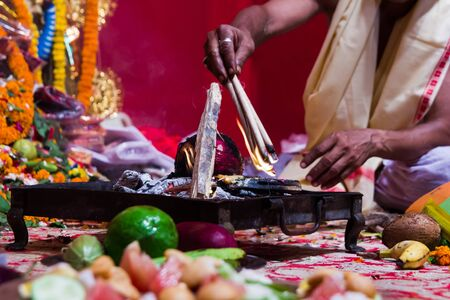 hand of a priest worshiping hindu god with fire and yagna ritual