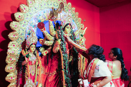 october, 2018, Kolkata, India. Bengali women greeting idol of godess durga with sweets and betel leaves in a very important ritual