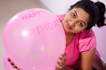 portrait of an indian girl dressed in pink dress with pink balloons on her birthday with selective focus on balloon