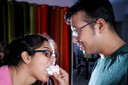 an young indian romantic couple feeding cake to each other Imagens